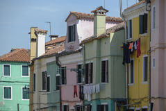 BURANO ITALIEN - APRIL 18, 2009: Gata med färgrika byggnader i den Burano ön, en artig liten stad mycket av kanaler, nära Venic Arkivbild