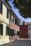 BURANO ITALIEN - APRIL 18, 2009: Gata med färgrika byggnader i den Burano ön, en artig liten stad mycket av kanaler, nära Venic Royaltyfria Foton