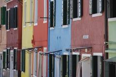 BURANO ITALIEN - APRIL 18, 2009: Gata med färgrika byggnader i den Burano ön, en artig liten stad mycket av kanaler, nära Venic Fotografering för Bildbyråer