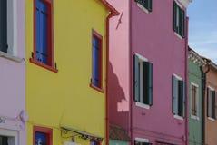BURANO ITALIEN - APRIL 18, 2009: Gata med färgrika byggnader i den Burano ön, en artig liten stad mycket av kanaler, nära Venic Arkivfoton