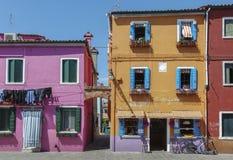 BURANO ITALIEN - APRIL 18, 2009: Gata med färgrika byggnader i den Burano ön, en artig liten stad mycket av kanaler, nära Venic Royaltyfri Foto
