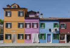 BURANO ITALIEN - APRIL 18, 2009: Gata med färgrika byggnader i den Burano ön, en artig liten stad mycket av kanaler, nära Venic Royaltyfria Bilder