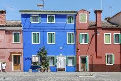 BURANO ITALIEN - APRIL 18, 2009: Gata med färgrika byggnader i den Burano ön, en artig liten stad mycket av kanaler, nära Venic Royaltyfri Fotografi
