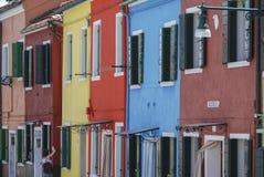 BURANO ITALIEN - APRIL 18, 2009: Gata med färgrika byggnader i den Burano ön, en artig liten stad mycket av kanaler, nära Venic royaltyfri bild