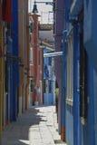 BURANO ITALIEN - APRIL 18, 2009: Gata med färgrika byggnader i den Burano ön, en artig liten stad mycket av kanaler, nära Venic Arkivfoto