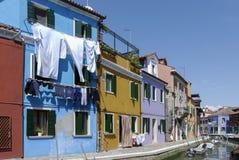 BURANO - ITALIEN, APRIL 18, 2009: Panoramautsikt av färgrika byggnader och fartyg framme av en kanal på Burano Royaltyfri Bild