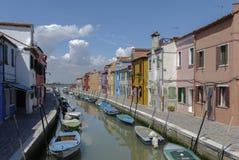 BURANO - ITALIEN, APRIL 18, 2009: Panoramautsikt av färgrika byggnader och fartyg framme av en kanal på Burano Royaltyfria Bilder
