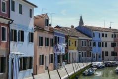 BURANO - ITALIEN, APRIL 18, 2009: Panoramautsikt av färgrika byggnader och fartyg framme av en kanal på Burano Royaltyfri Fotografi