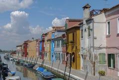 BURANO - ITALIEN, APRIL 18, 2009: Panoramautsikt av färgrika byggnader och fartyg framme av en kanal på Burano Fotografering för Bildbyråer