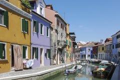 BURANO - ITALIEN, APRIL 18, 2009: Panoramautsikt av färgrika byggnader och fartyg framme av en kanal på Burano Royaltyfri Foto