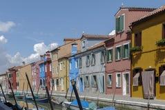 BURANO - ITALIEN, APRIL 18, 2009: Panoramautsikt av färgrika byggnader och fartyg framme av en kanal på Burano arkivbild