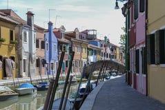 BURANO - ITALIEN, APRIL 18, 2009: Panoramautsikt av färgrika byggnader och fartyg framme av en kanal på Burano Arkivfoton