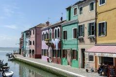 BURANO - ITALIEN, APRIL 18, 2009: Panoramautsikt av färgrika byggnader, oidentifierat folk och fartyg framme av en kanal på Buran Royaltyfri Bild