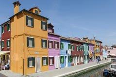 BURANO - ITALIEN, APRIL 18, 2009: Panoramautsikt av färgrika byggnader, oidentifierat folk och fartyg framme av en kanal på Buran Arkivbild