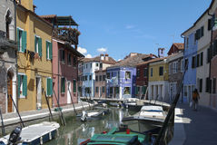 BURANO - ITALIEN, APRIL 18, 2009: Panoramautsikt av färgrika byggnader, oidentifierat folk och fartyg framme av en kanal på Buran Arkivfoto