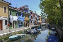 BURANO - ITALIEN, APRIL 18, 2009: Panoramautsikt av färgrika byggnader, oidentifierat folk och fartyg framme av en kanal på Buran Arkivfoton