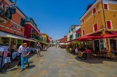 BURANO ITALIEN - JUNI 14, 2015: Colorfull gata med hus på sidan av olika färger, turists som tycker om sommar Arkivbild