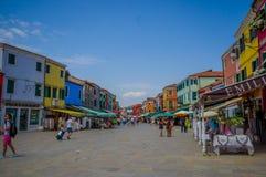 BURANO ITALIEN - JUNI 14, 2015: Nice shoppar gatan i den Burano staden, turists som tycker om en varm dag under sommar Royaltyfria Foton