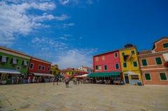 BURANO ITALIEN - JUNI 14, 2015: Nice shoppar gatan i den Burano staden, turists som tycker om en varm dag under sommar Royaltyfri Foto