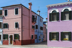 BURANO - ITALY, APRIL 18, 2009: Panoramic view of colorful buildings and boats in front of a canal at Burano royalty free stock photos