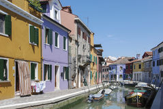 BURANO - ITALY, APRIL 18, 2009: Panoramic view of colorful buildings and boats in front of a canal at Burano Royalty Free Stock Photo