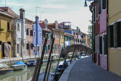 BURANO - ITALY, APRIL 18, 2009: Panoramic view of colorful buildings and boats in front of a canal at Burano Stock Photos