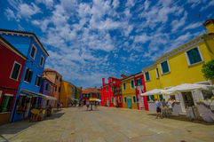 BURANO, ITALY - JUNE 14, 2015: Large perspective full color houses photo in Burano, stone path with tourists Stock Photos