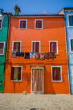 BURANO, ITALY - JUNE 14, 2015: Little house in orange color, various windows and wet clothes outside Stock Photo