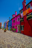 BURANO, ITALY - JUNE 14, 2015: Vertical photos of colorfull houses at Burano, pinturesque street that ends with fresh Royalty Free Stock Images