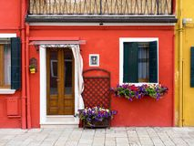 Burano, Italy - 21 May 2015: Red painted building. One of the ma. Ny different coloured painted buildings on the island of Burano near Venice, Italy Royalty Free Stock Image