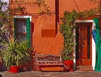 Burano, Italy - painted house with bench and plants. Burano, Italy, small island and fisher village in the Venetian lagoon, famous for the striking colors of its royalty free stock photo