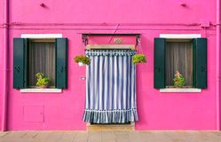 BURANO, ITALY - 2 September, 2016. Pink color of the walls, two windows, flowers on the windowsill. Typical view of Burano islan royalty free stock image