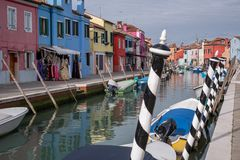 Typical street scene showing brighly painted houses, mooring posts and canal on the island of Burano, Venice. Burano, Italy. Typical street scene showing black Stock Images