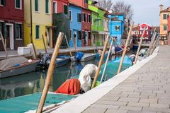 Typical street scene showing brighly painted houses, mooring posts and canal on the island of Burano, Venice. Burano, Italy. Typical street scene showing Royalty Free Stock Photo