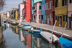 Burano, Italy. Typical street scene showing brightly painted houses reflected in the canal, with boats. Photographed on a sunny day Royalty Free Stock Images