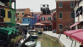 BURANO - JULY 14: Real time establishing shot of a canal with colorful houses on the island of Burano. Burano island is stock video