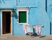 Burano, Laundry in the sun. A beautiful day of September in Burano near Venice, a little light blue house with the washing in the sun, a quiet place to remenber stock photo