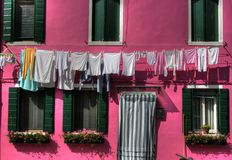 Burano laundry, Venice. Laundry hanging on a clothesline in front of a bright pink house in burano italy Stock Image