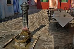 Burano - part view from one street with old fountain Royalty Free Stock Image