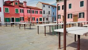 Burano, VENICE, Italy - May 2019: Empty tables of the city market and colorful houses. The concept of siesta and lack of