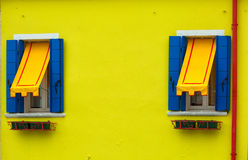 Burano, Venice. Two windows with blue shutters and awnings on the yellow wall, Burano, Venice Stock Images