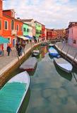 Burano wyspy malownicza ulica z małymi barwionymi domami w rzędzie, wodny kanał z fishermans łodziami, chmurny niebieskie niebo obrazy royalty free