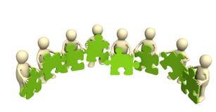 Burattini, tenenti in mani un puzzle di colore verde Fotografia Stock