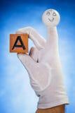Burattino del dito che tiene cubo di legno con la lettera maiuscola A Fotografia Stock Libera da Diritti