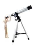 Burattino di legno osservando con il telescopio Fotografie Stock Libere da Diritti