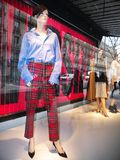 Burberry Showcase at Printemps Haussmann store Paris. Burberry showcase displaying womenswear as a red Tartan troussers on a mannequin at the Printemps stock photo