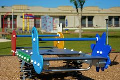 Burbscape the Places we Play. Abstract presentation of outdoor play structure in suburban community, with community school in background Stock Photography