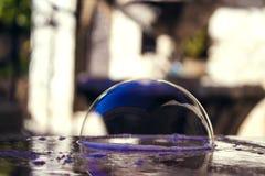 Burbuja de jabón brillante en la tabla de piedra imagen de archivo