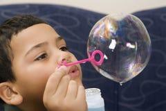 Burbuja de jabón del muchacho que sopla. imagen de archivo libre de regalías