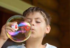 Burbuja de jabón del muchacho que sopla Fotografía de archivo libre de regalías